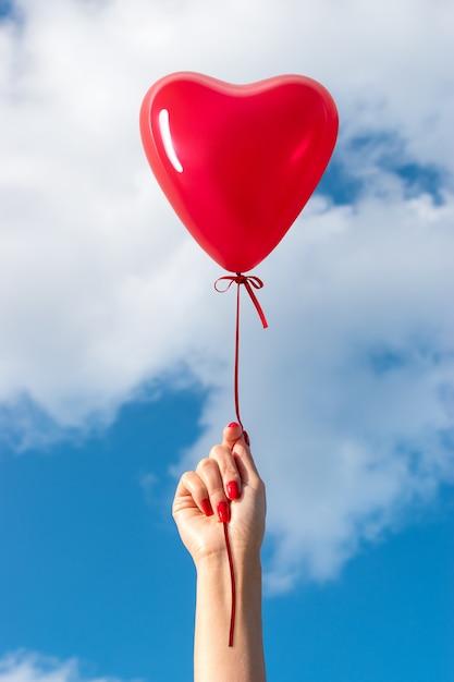 空の背景にハート型の風船で女性の手。 Premium写真