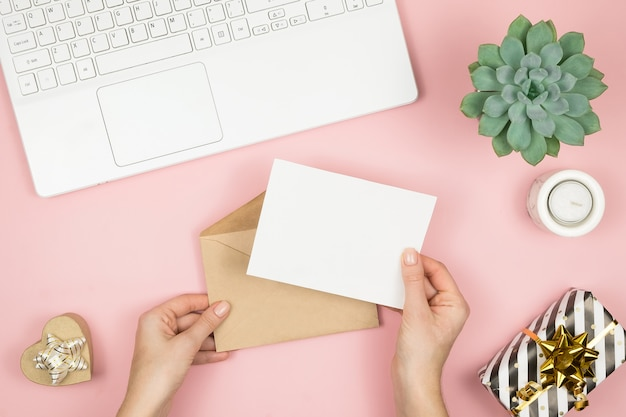 Womans hands holding craft envelope with copyspace on pink pastel table top view. flat lay composition for valentines day. Premium Photo