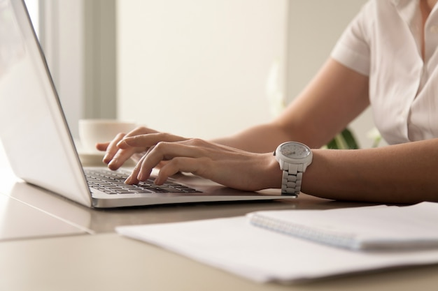 Womans hands typing on laptop at workplace Free Photo