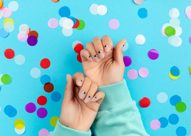 Womans hands with colorful confetti over blue background. beauty fashion spa salon concept Premium Photo