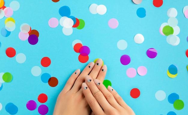 파란색 배경 위에 화려한 색종이와여 대 손. 뷰티 패션 스파 살롱 개념 프리미엄 사진