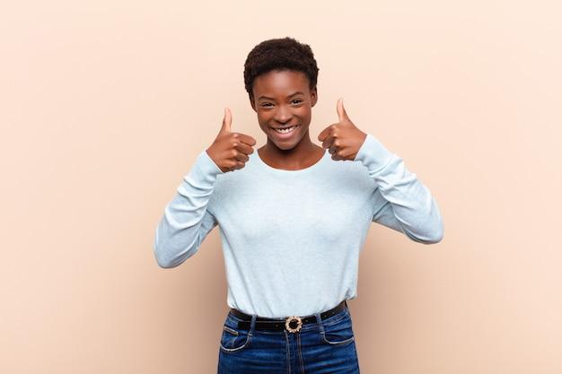 両方の親指で幸せ、肯定的、自信を持って、成功して広く見ている若いかなり黒womansmiling Premium写真