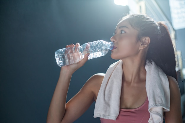 Women after exercise drink water from bottles and handkerchiefs in the gym. Free Photo