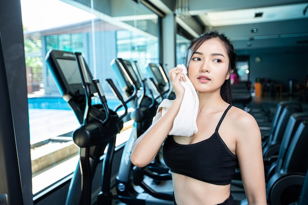 Women after exercising, wipe the face with a white cloth in the gym. Free Photo
