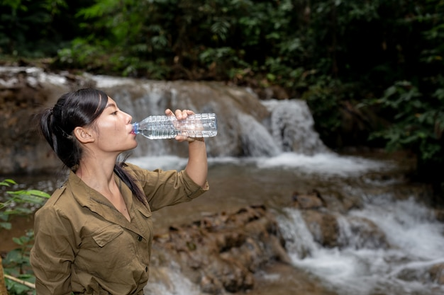 Women are hiking drinking fresh water in the forest Free Photo