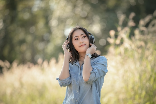 Women asian girl with headphones listening bluetooth digital music in the park and grass bokeh background Premium Photo