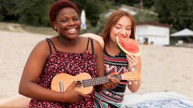 Women at the beach enjoying watermelon and playing guitar Free Photo