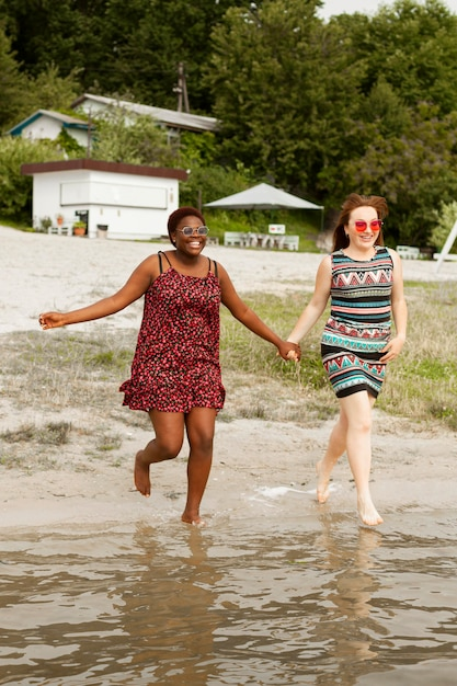 Women at the beach holding hands and running in the water Free Photo