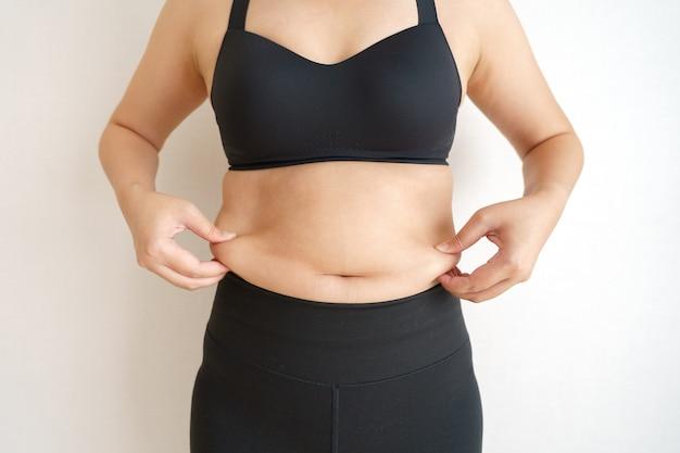 여성 체지방 배. 과도한 배꼽 지방을 들고 뚱뚱한 여자 손. 다이어트 라이프 스타일 개념 프리미엄 사진
