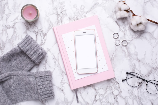 Women business day with mobile phone and pink notebook on marble table Premium Photo