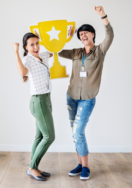 Women celebrating their success with a trophy Free Photo