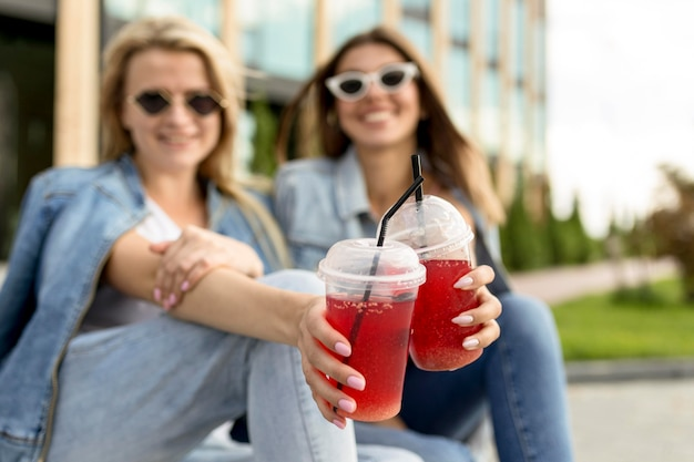Women cheering with red smoothies Free Photo