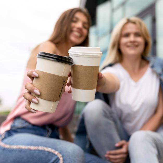 Donne che esultano con le loro tazze di caffè Foto Gratuite