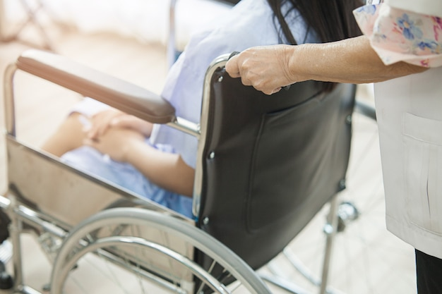 Women doctor is wheelchair in which a young patient is sitting in the hospital Premium Photo
