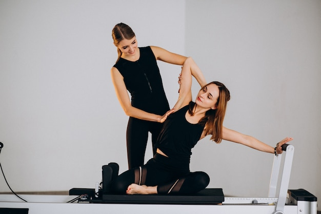 Women doing pilates on a reformer Free Photo
