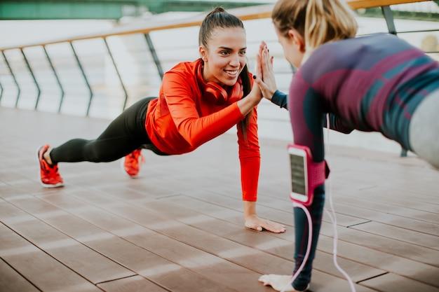 Women doing plank on riverside after running Premium Photo