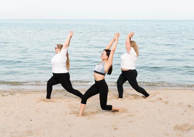 海のそばでストレッチ体操をしている女性 無料写真