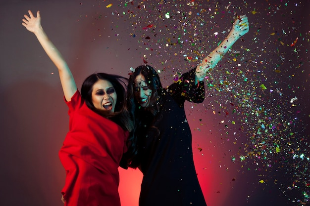 Women dressed as witches with confetti Free Photo
