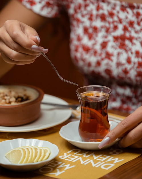 レモンと伝統的なアゼルバイジャングラスで紅茶を飲む女性 無料写真