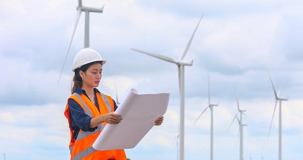 Women engineer working on site at wind turbine farm Premium Photo