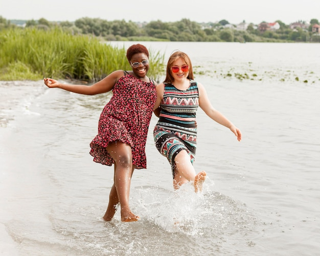 Women enjoying the water together at the beach Free Photo