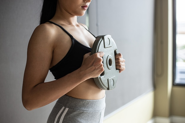 Women exercise with dumbbell weight plates in the chest. Free Photo