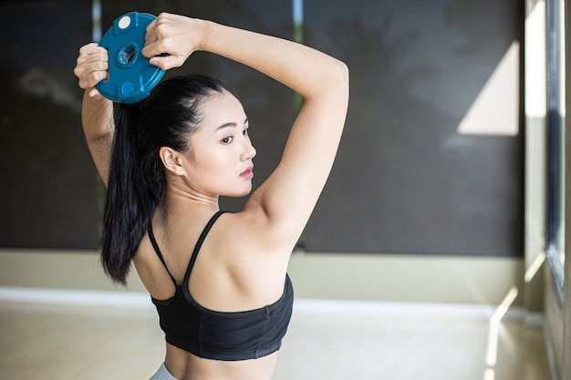 Women exercise with dumbbell weight plates and twist to the back. Free Photo