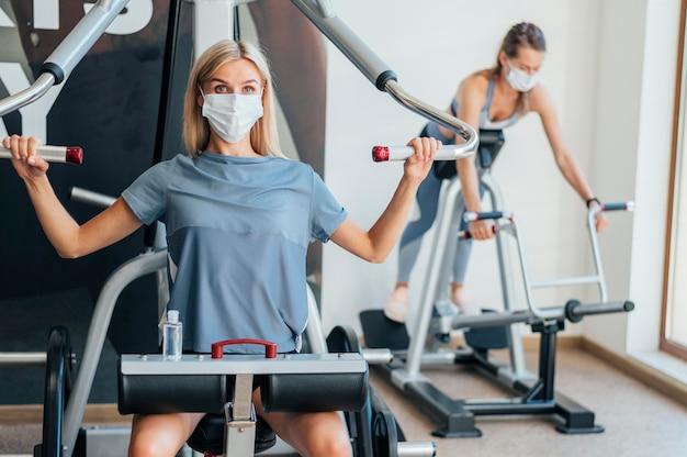 Женщины, тренирующиеся в тренажерном зале с оборудованием и маской Бесплатные Фотографии