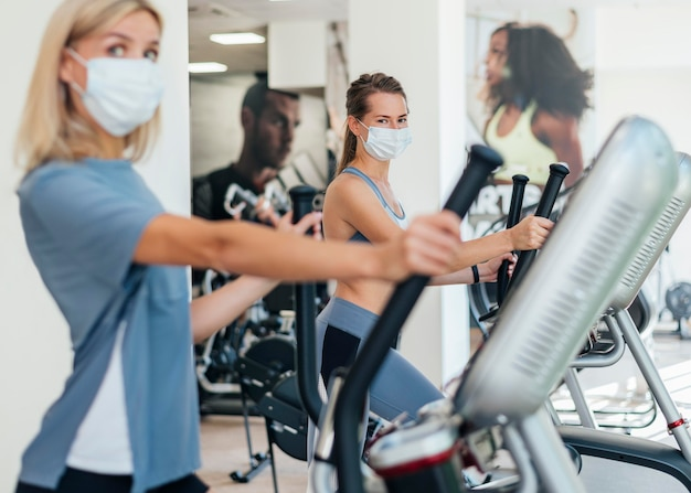 Женщины, тренирующиеся в тренажерном зале с маской Бесплатные Фотографии