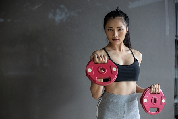 Women exercising with two dumbbell weight plates Free Photo