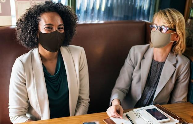 Donne in maschera facciale al bar durante la pausa pranzo Foto Gratuite
