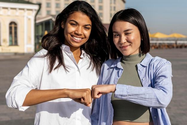Women fist bumping outdoors Free Photo