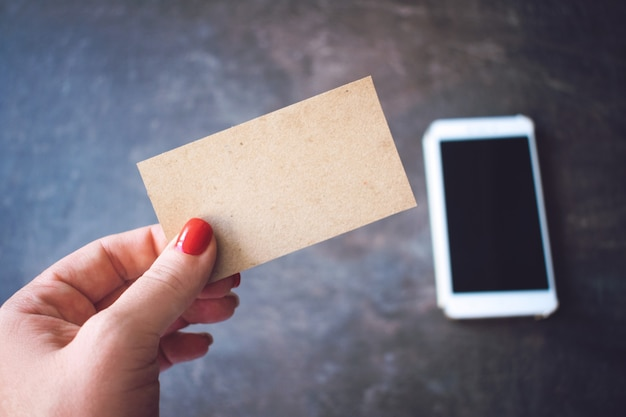 Women hand holding recycled paper blank business card on defocused smartphone Premium Photo