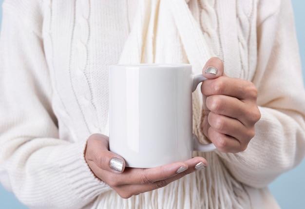 白いセラミックコーヒーカップを持つ女性の手。創造的な広告テキストメッセージまたはプロモーションコンテンツのモックアップ。 Premium写真