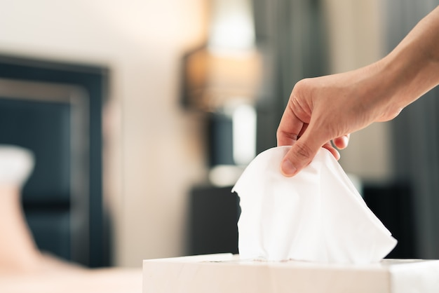 Women hand picking tissue paper from the tissue box Premium Photo