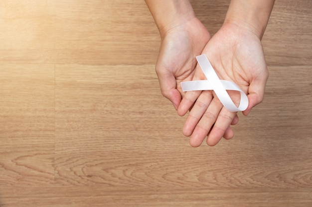 Women hands holding white bow, white ribbons on wooden background. Premium Photo