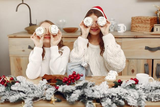 女性はカップケーキを持っています。クリスマスの装飾の友達。サンタの帽子をかぶった女の子。 無料写真
