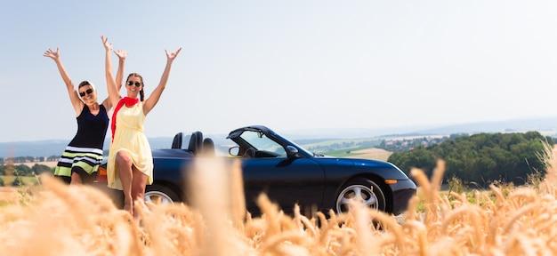 Women having joyride in convertible car having rest Premium Photo