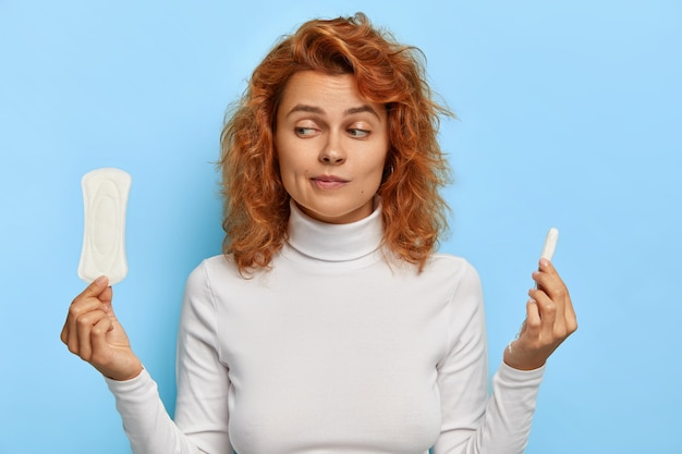 Women health care and hygiene concept. indoor shot of hesitant young ginger woman holds two intimate products, chooses between tampon and pad during menses, thinks what gives better protection Free Photo