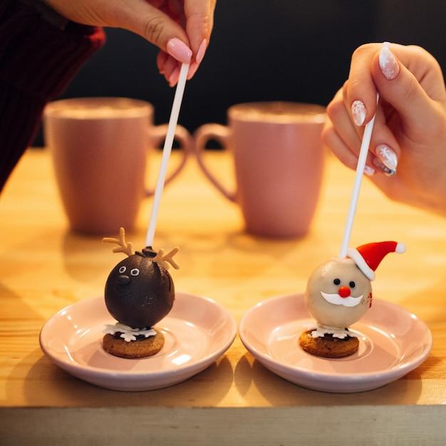 女性はクリスマスのデザインのお菓子とピンクのプレートの棒を保持 無料写真