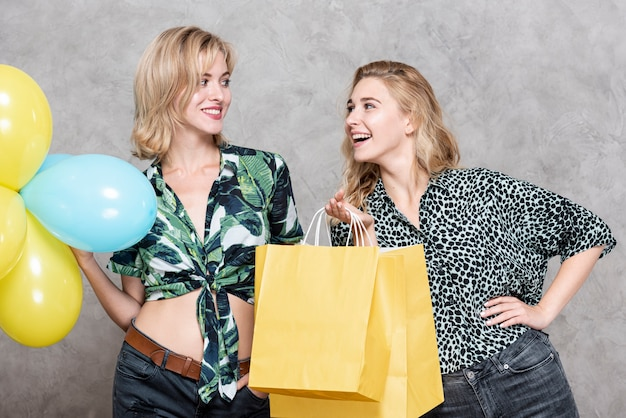 Women holding balloons and paper bags Free Photo