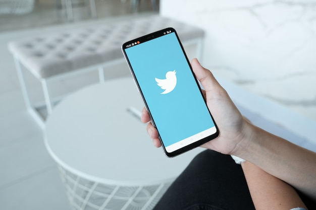 Women holding smartphone with twitter logo on the screen. twitter is a social media online service for microblogging and networking communication. Premium Photo
