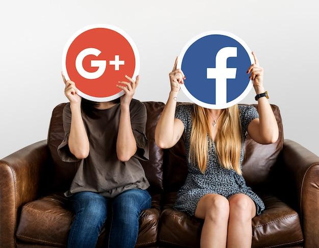 Women holding social media icons Free Photo