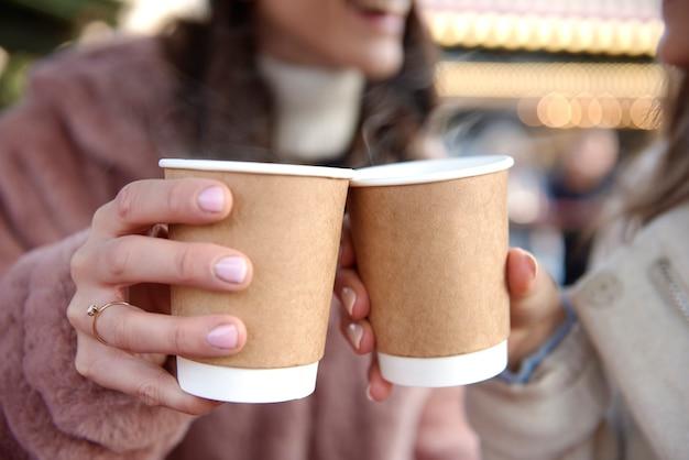 グリューワインと2つのカップを保持している女性 無料写真