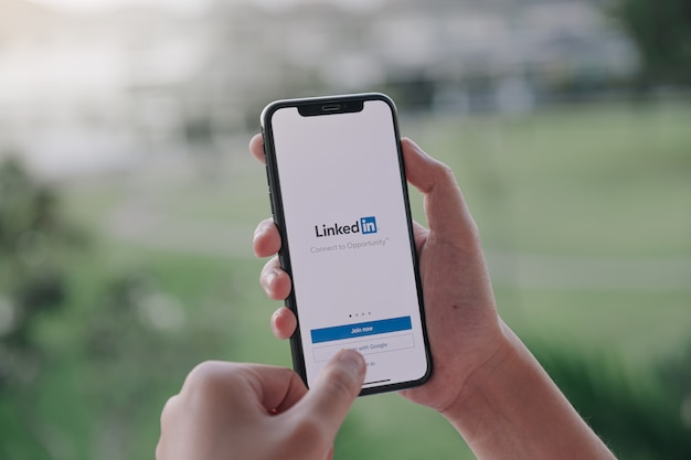 A women holds smartphone with linkedin application on the screen Premium Photo