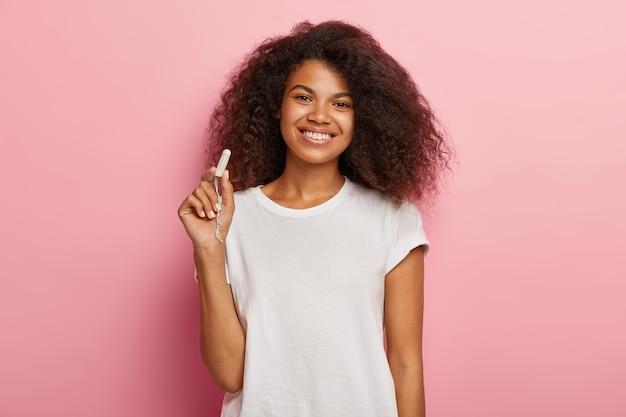 女性の衛生保護の概念。陽気な暗い肌の女性は綿のタンポンを保持します 無料写真