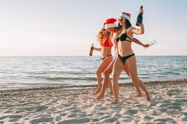 Женщины в бикини с шляпой санты и шампанским Premium Фотографии