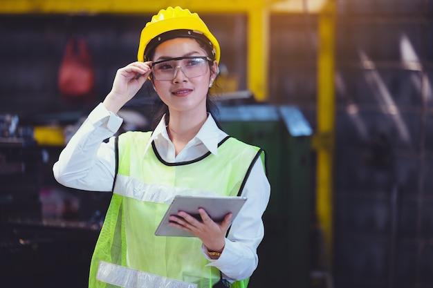 タブレットを手にした女性の産業プラント、工場での産業機械のセットアップで働くことを探しているエンジニア。 Premium写真