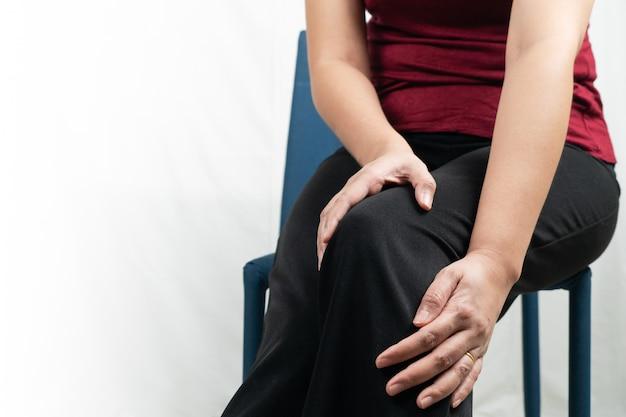 У женщин болит колено, женщины касаются боли в колене дома Premium Фотографии