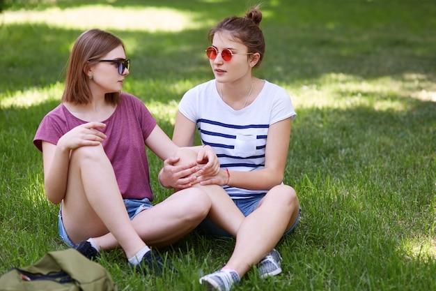 緑の芝生で組んだ足に座って、お互いに愛情を込めて見て、サングラスをかけている間、女性レズビアンは一緒に楽しみます Premium写真